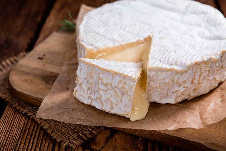 Pieza de queso camembert sobre una tabla de madera