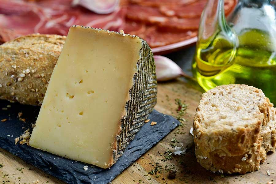 Tabla con cuña de queso manchego, aceite, pan y jamón serrano