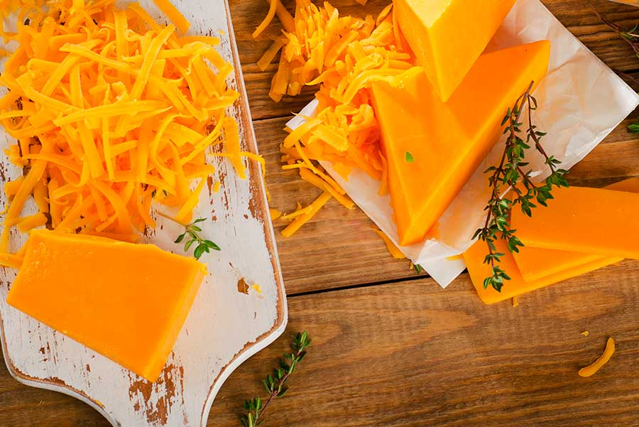 Pieza de queso cheddar en piezas y rallado