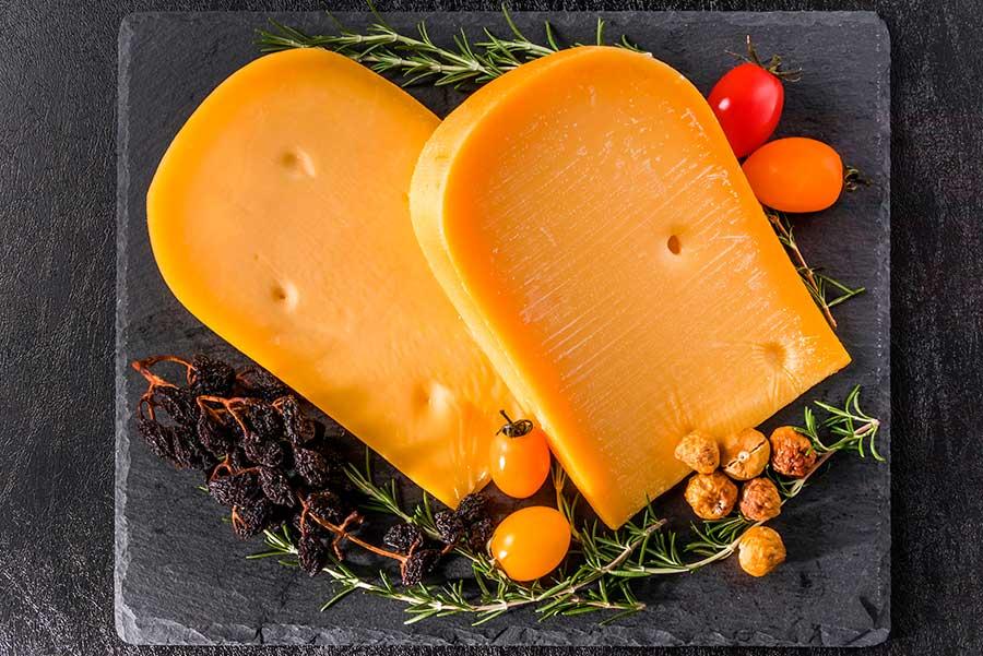 Dos piezas de queso gouda sobre una tabla