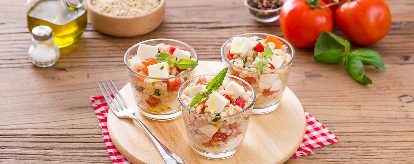 Tres vasitos de ensalada de arroz con mozzarella, tomate y albahaca.