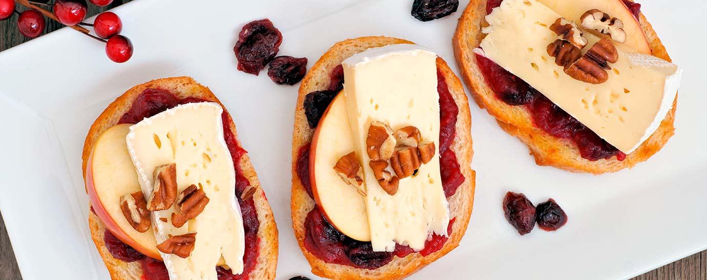Tres tostas con queso brie con nueces sobre un plato.