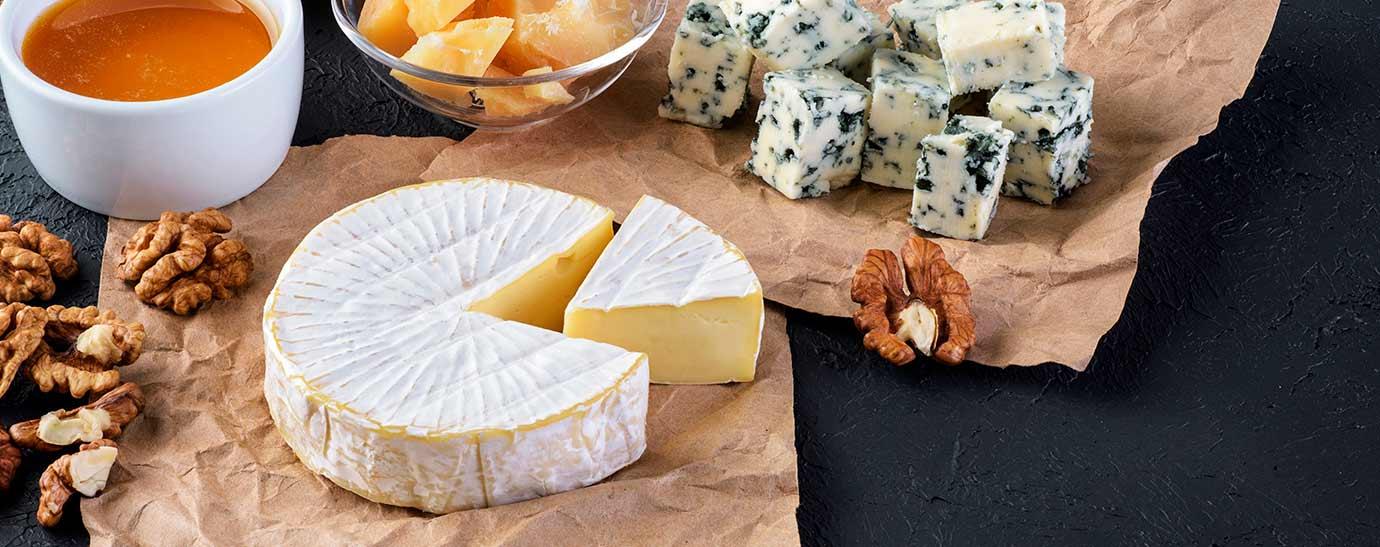 Queso camembert, parmesano y queso azul sobre papel. Servido con bol de miel y nueces.