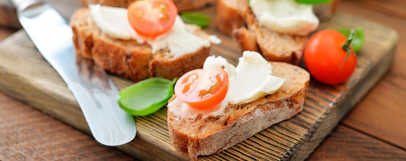 Queso Flor de Esgueva untado en tostadas de pan con tomate cherry y albahaca