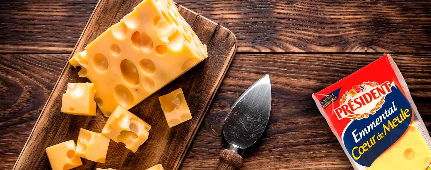 Una cuña de queso emmental que tiene una parte cortada en daditos y desparramados sobre la madera en la que reposa y un pack de emmental Président