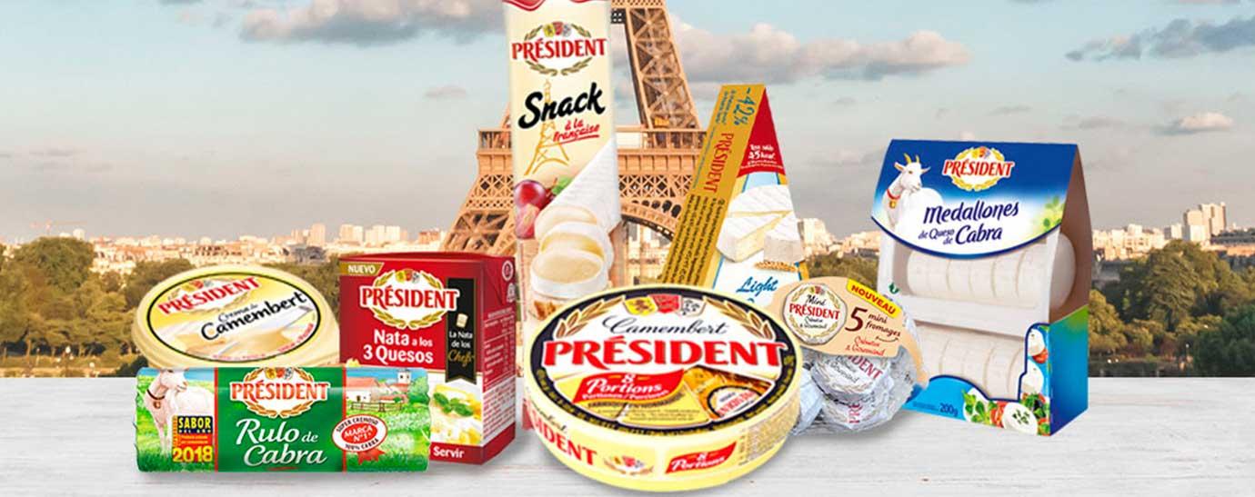 Bodegón de productos Président sobre una mesa de madera blanca y de fondo la Torre Eiffel