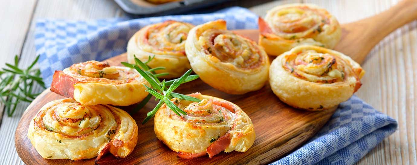 Tabla de madera con rollitos de hojaldre de jamón y queso sobre un paño e una mesa de cocina.