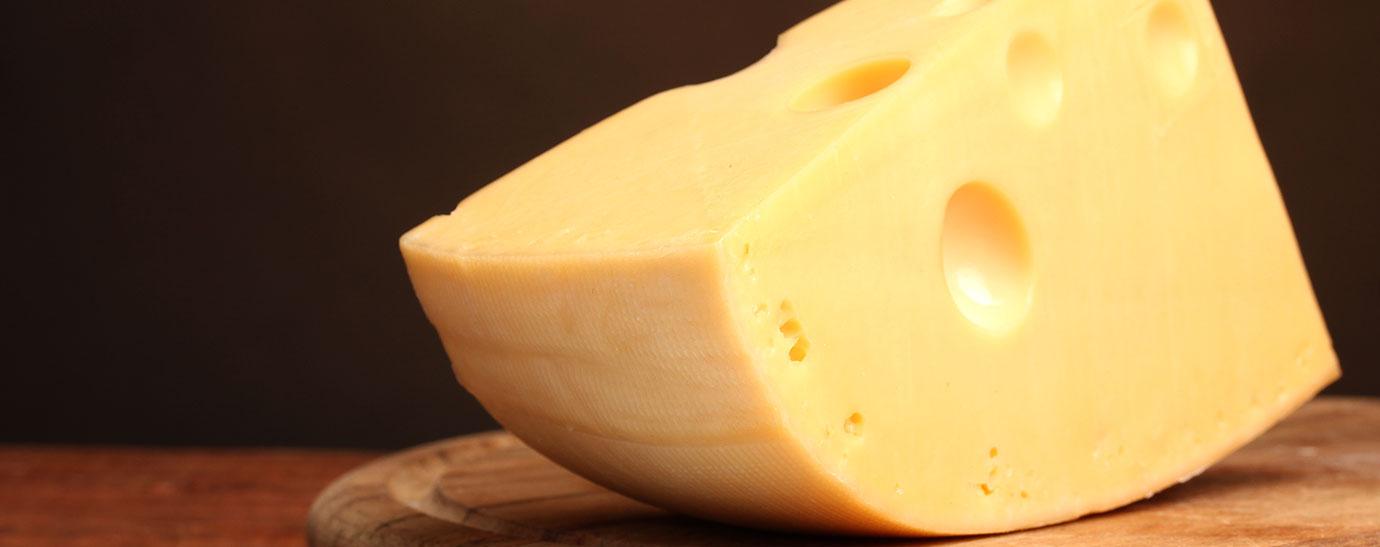Cuña de queso cortada sobre una tabla de madera